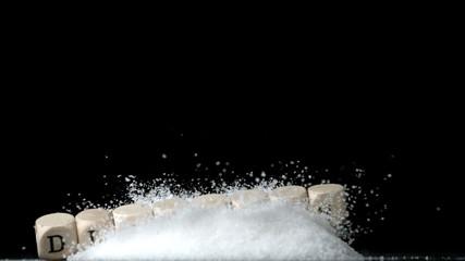 Dice spelling diabetes falling over sugar on black background