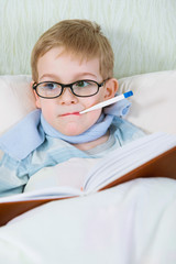 Sick little boy lying in bed with thermometer