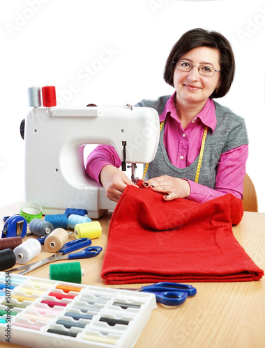 Woman worker sews on the sewing machine.
