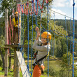 Woman climbing rope ladder in adventure park