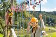 Woman climbing on rope ladder adrenalin park