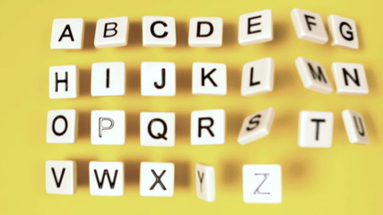 Plastic letters bouncing and showing alphabet on yellow surface