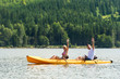 Man and woman kayaking on pond vacation