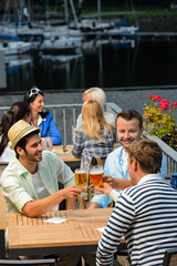 Three men drinking beer at terrace bar