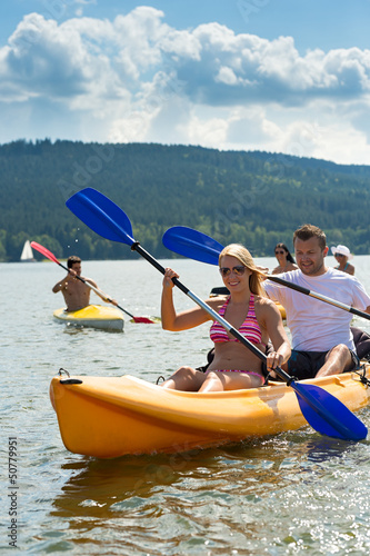Smiling couple rowing kayak sunshine