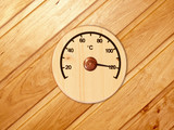 the wooden thermometer hanging in a sauna on a wall