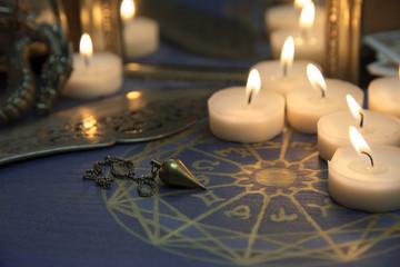 Astrologischer Kreis im Kerzenschein mit Pendel und Spiegel