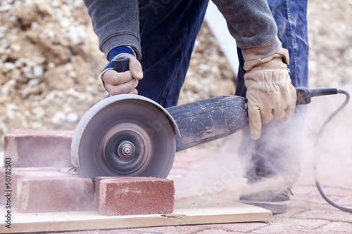 worker uses a stone cutter to cut the brick pavers