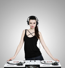 Beautiful brunette woman with headphones and turntables