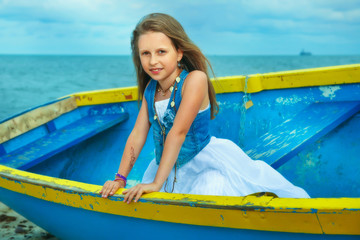 Little cute girl in a boat on the beach, vacation day.