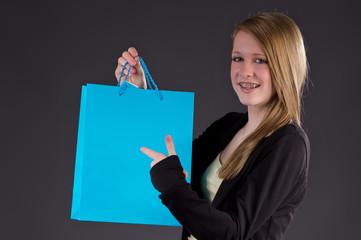 Hübsches Mädchen deutet auf blauen Shoppingbag