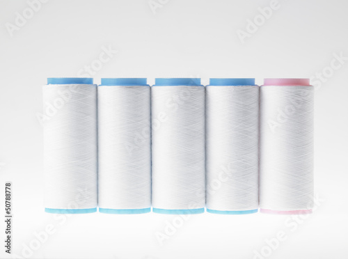 White on white, spools of thread on white background