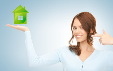 woman pointing her finger at green eco house