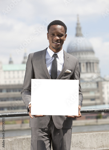 Portrait of African American businessman smiling and holding blank cardboard