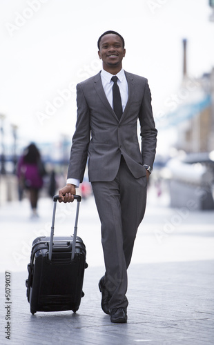 Portrait of African American businessman smiling and pulling suitcase
