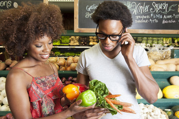 Young African American couple buying vegetables at supermarket