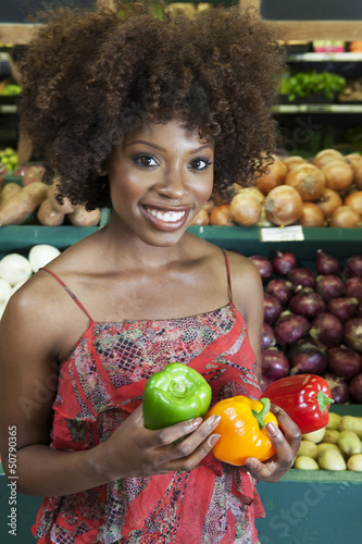African American woman holding bell peppers at supermarket