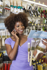 African American woman buying paint Brushes at hardware store