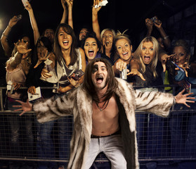 Portrait of young man in fur coat screaming with excited audience in the background