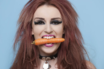 Portrait of funky young woman holding carrot in mouth over blue background
