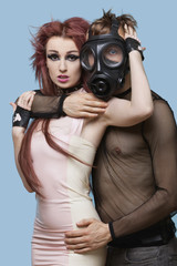 Portrait of young man in gas mask embracing funky woman over blue background