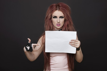 Portrait of arrogant young funky woman pointing towards blank placard against black background
