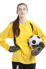 Portrait of young female soccer player holding ball with hand on hip against white background
