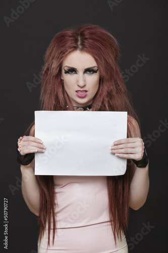 Portrait of arrogant young funky woman with blank placard standing against black background