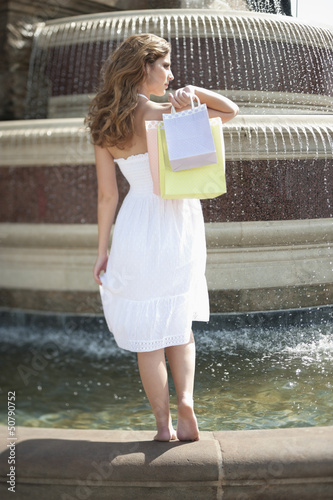 Back view of a young woman standing by fountain carrying shopping bags
