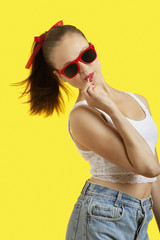 Portrait of playful young woman in sunglasses eating lollipop over yellow background