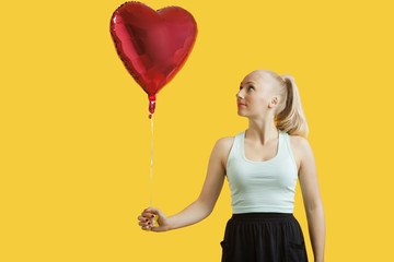 Beautiful young woman looking at heart shaped balloon over yellow background