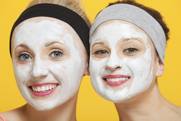 Portrait of two happy women with face pack on their faces over yellow background