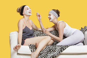Two happy young women applying face pack while sitting on sofa over yellow background