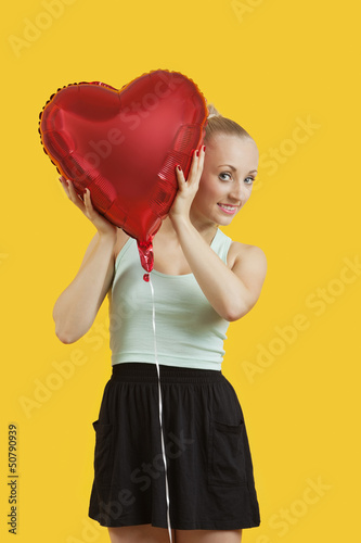 Portrait of beautiful young woman peeking through heart shaped balloon over yellow background