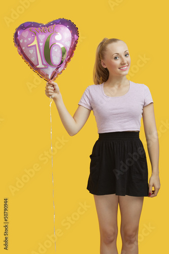 Portrait of beautiful young woman holding heart shaped birthday balloon over yellow background