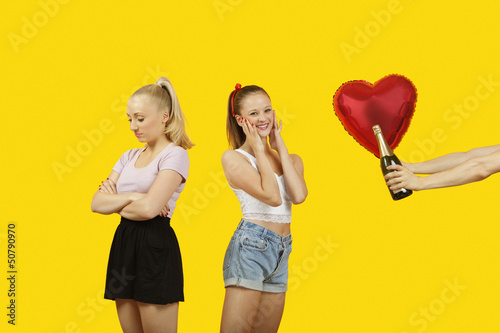 Man's hand gifting heart shaped balloon and champagne bottle to surprised woman with friend feeling left out standing behind