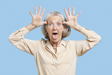 Portrait of senior woman making funny faces with hands on head against blue background