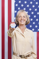 Portrait of senior woman holding election badge against American flag