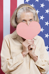 Portrait of senior woman with red paper heart against American flag
