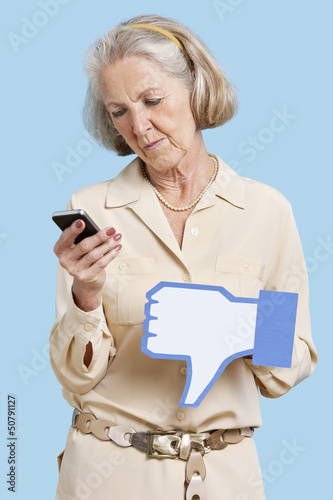Senior woman with cell phone holding fake dislike button against blue background