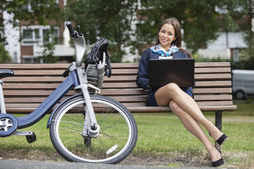 Portrait of young businesswoman with laptop sitting on bench at park