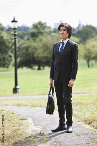 Young businessman carrying briefcase standing at park