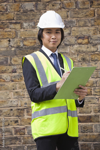 Portrait of young supervisor holding clipboard at construction site