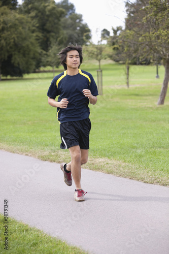 Young Chinese man jogging at park