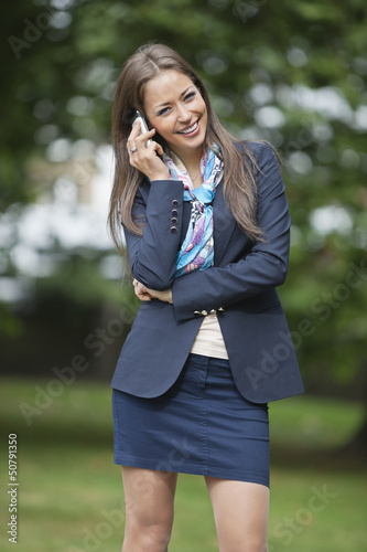 Portrait of happy businesswoman using cell phone at park