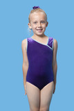 Portrait of a happy female gymnast standing over blue background