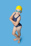 Portrait of a confident young girl in swimwear over blue background