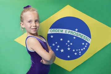 Portrait of a happy young female gymnast with arms crossed standing in front of South American flag