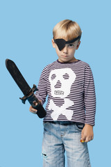 Portrait of a young boy in pirate costume holding sword over blue background