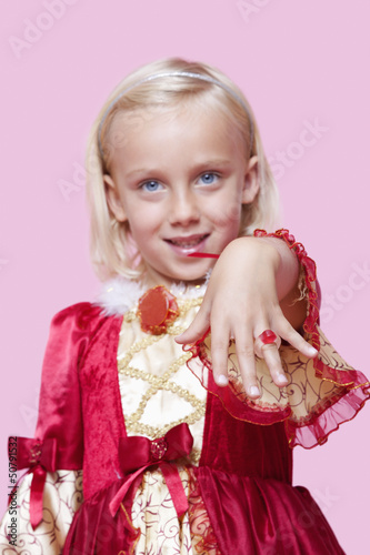 Portrait of a happy young girl dressed in princess costume displaying ring over pink background